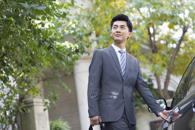 Young businessman opening car door