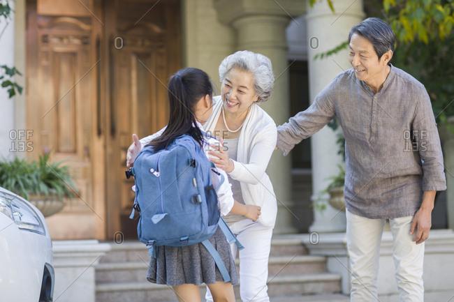 Schoolgirl running into grandmother's arms