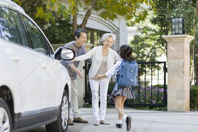 Schoolgirl running towards to her grandparents