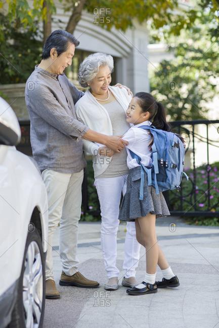 Little schoolgirl and her grandparents