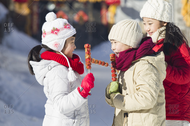 Happy children eating candied haws
