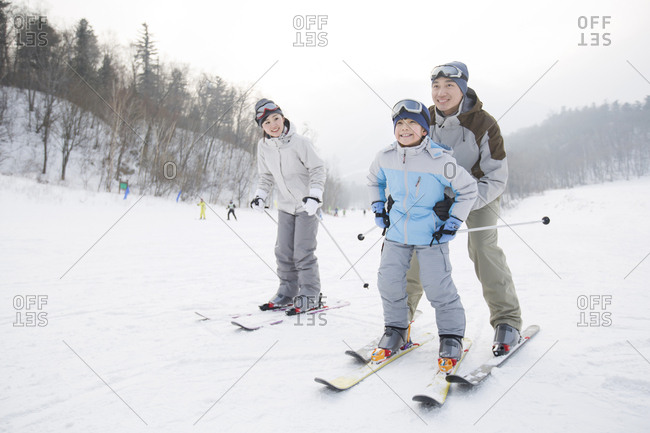 Young parents teaching son to ski