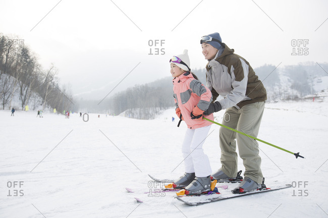 Young father teaching daughter to ski