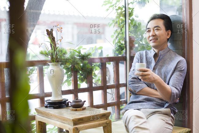 Mature man drinking tea in tea room