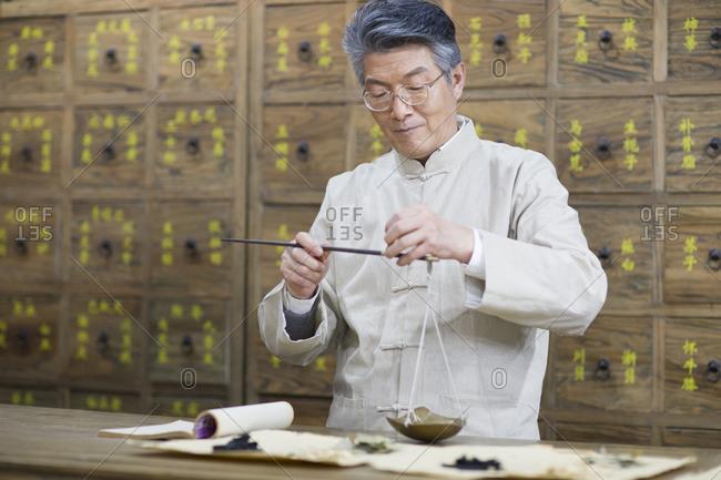 Senior Chinese doctor fill the prescription