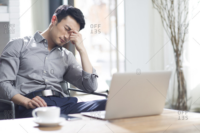 Tired young man rubbing eyes in office