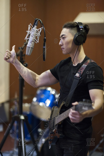Young man singing with guitar in recording studio