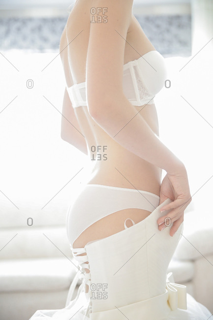 Woman in lingerie putting on wedding gown