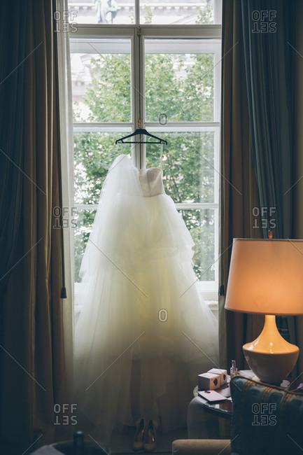 Wedding dress and veil hanging in window