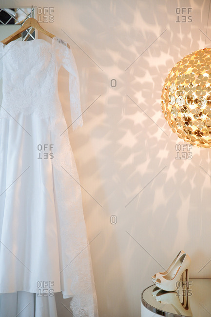 Wedding dress hanging from door frame next to modern light fixture