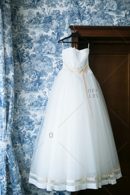 Strapless wedding dress hanging from wardrobe