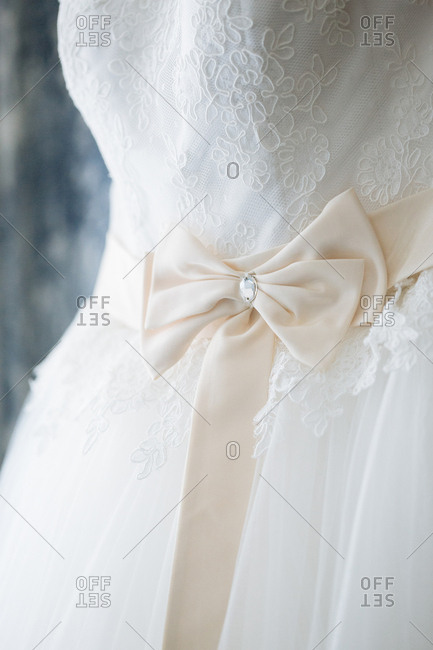 Close-up of off-white ribbon around waist of lace bridal gown