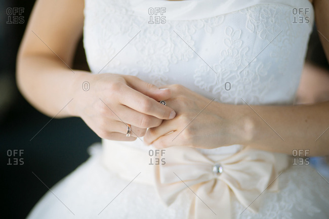 Close-up of bride in lace wedding dress with off-white ribbon around waist
