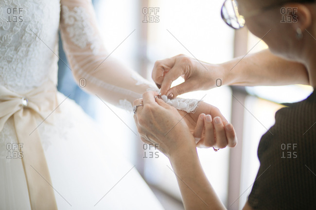 Woman helping bride button her lace sleeves