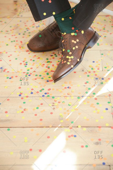 Man sitting with confetti on his dress shoes