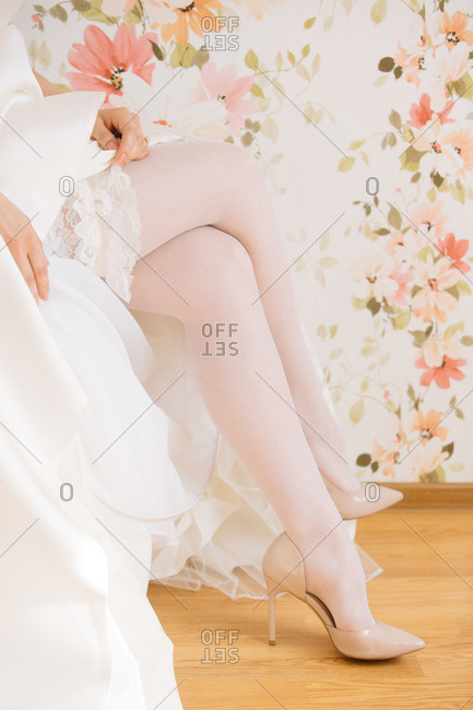 Bride with legs crossed adjusts garter