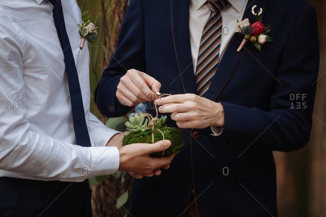 Man tying wedding band with string