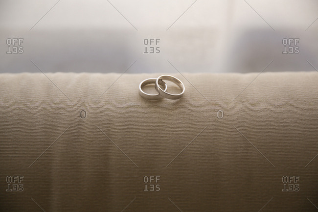 Two white gold wedding rings on cushion