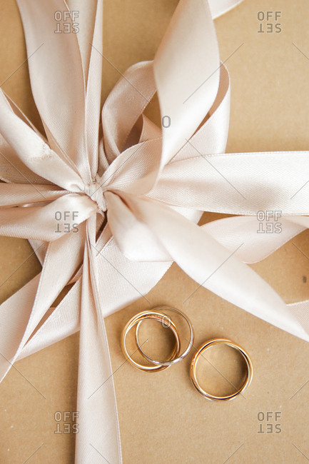 Wedding rings on brown paper tied with satin ribbon