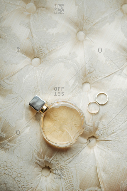 Bottle of perfume on cushion with wedding rings