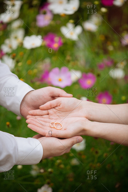 Man holding woman's hands with two wedding rings