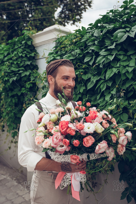 Portrait of a groom standing on a sidewalk holding bouquet