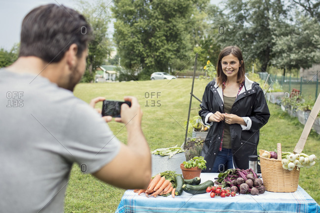 Mid adult man photographing woman standing at table full of garden vegetables