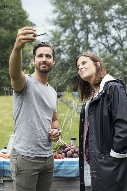 Mid adult couple taking selfie through mobile phone in urban garden