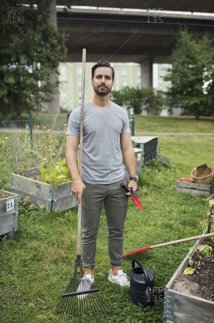 Full length portrait of mid adult man with rake and trowel in urban garden