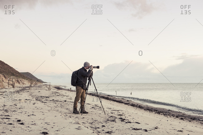 Full length side view of hiker photographing through SLR camera on shore at beach