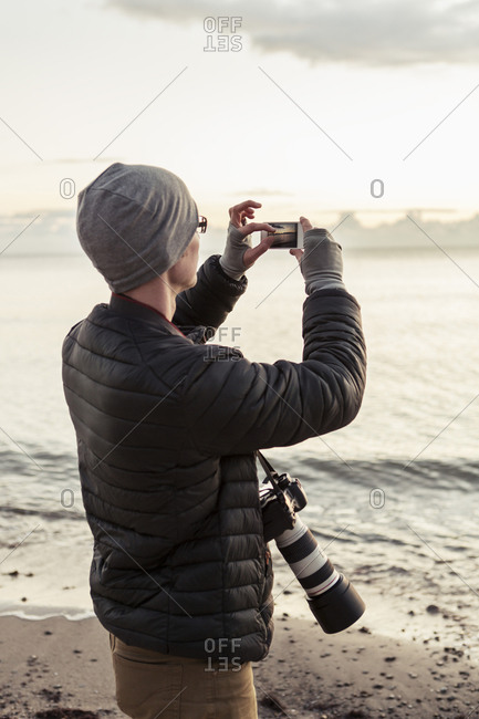Hiker photographing through smart phone at beach