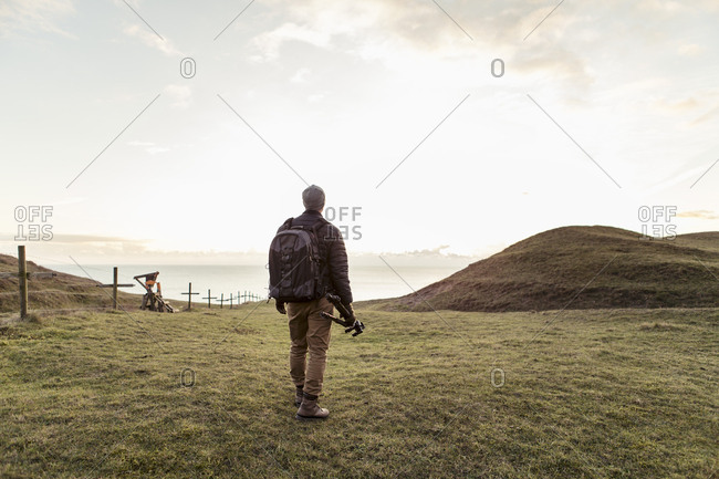 Rear view of hiker holding tripod while walking on field against sky