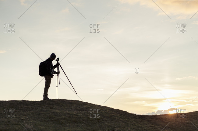 Side view of silhouette hiker fixing tripod on hill against sky during sunset