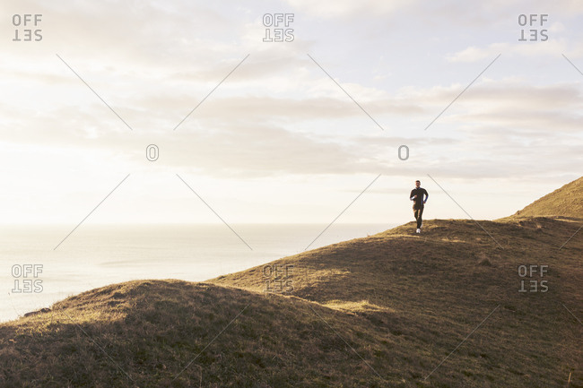 Mid distance of man jogging on hill by sea during sunny day