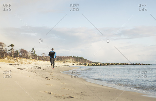 Rear view of man jogging on shore at beach against cloudy sky
