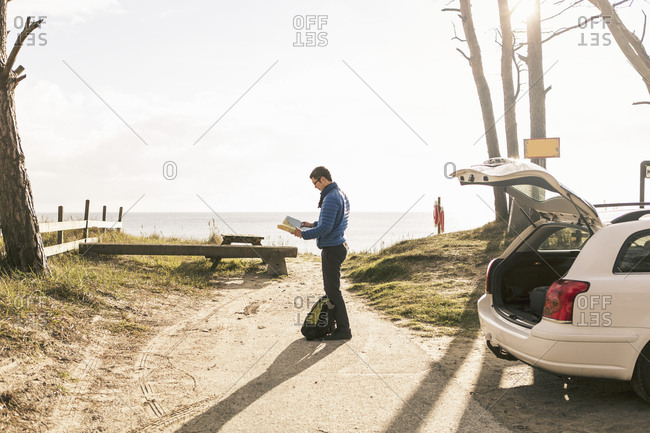 Full length of man reading map while standing on footpath at beach