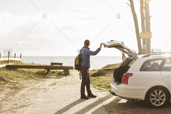 Side view of man carrying backpack while standing by car on footpath
