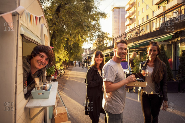 Portrait of happy customers and food truck owner on street