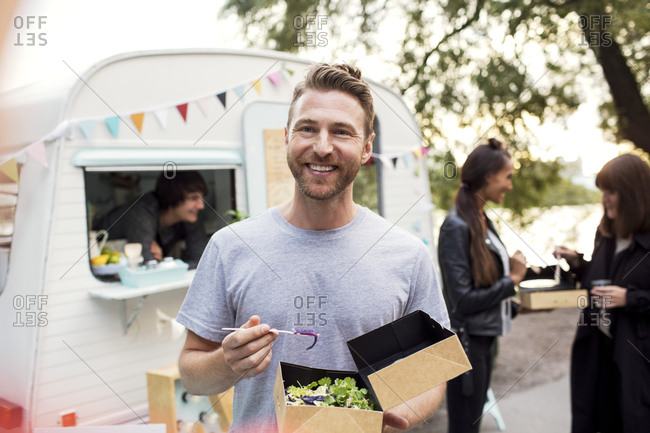 Smiling male customer holding disposable salad box against food truck with friends and owner in background