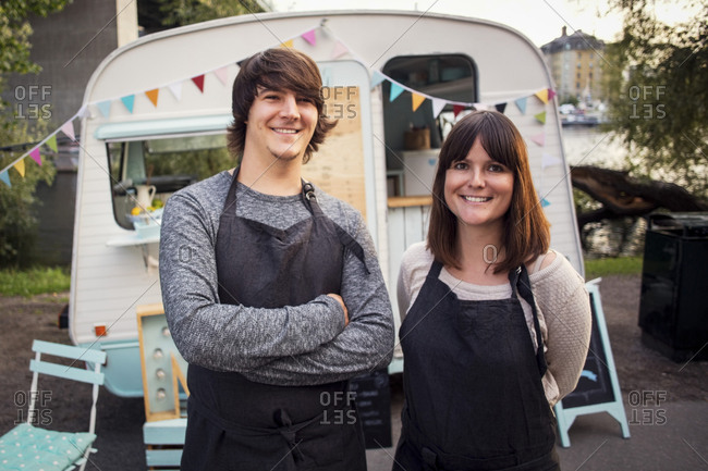 Portrait of happy owners standing on street against food truck
