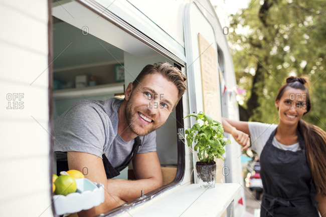 Happy male and female food truck owners looking away