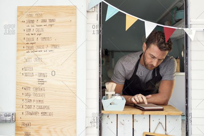 Male owner using digital tablet at food truck window