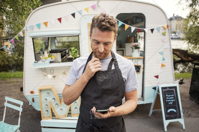 Male owner using smart phone while standing on street against food truck