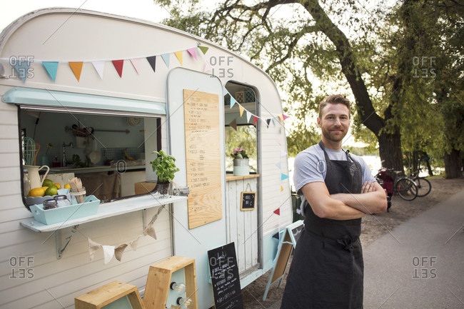 Portrait of confident owner standing arms crossed outside food truck on street