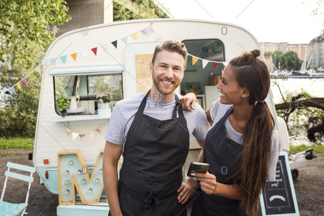 Portrait of happy owner standing with female colleague outside food truck on street