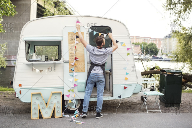Full length rear view of male owner hanging bunting on food truck