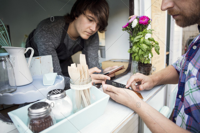 Midsection of male customer paying through card reader while owner holding digital tablet at food truck