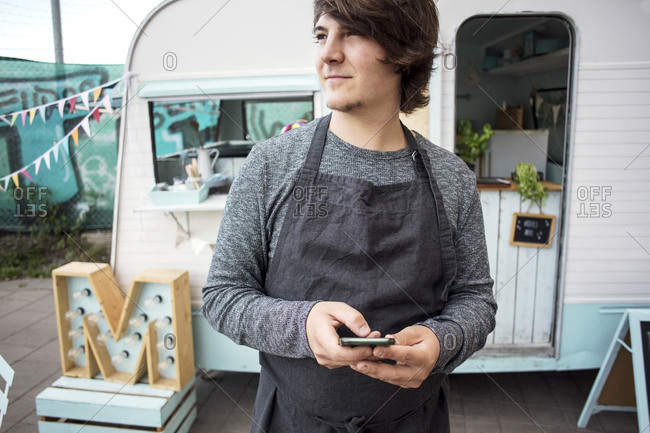 Thoughtful male owner holding smart phone while standing against food truck