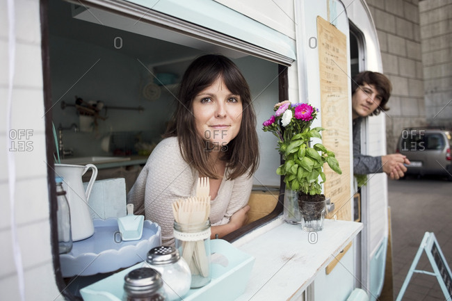 Portrait of male and female owners leaning on food truck windows