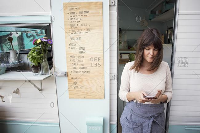 Female owner using smart phone outside food truck